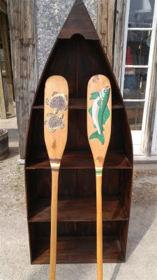Wood Canoe Bookcase with a rich finish, 2 paddles painted with turtles and fish on either paddle